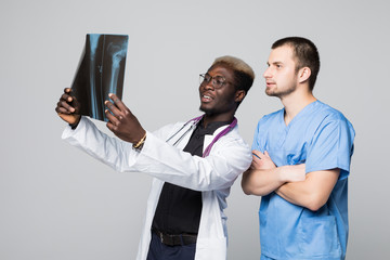 healthcare, medical and radiology concept - two doctors looking at x-ray on gray background