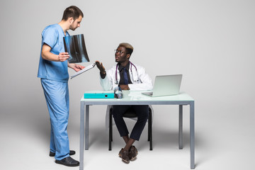 Young doctors discussing diagnosis in bright office. Two doctors disscusing xray at office table isolated on white background