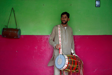 Safeer practises playing the dhol, an Indian musical instrument, in his room in Karachi