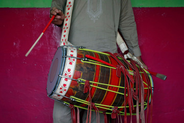 Safeer strikes a dhol, an Indian musical instrument, as he practises in his room in Karachi