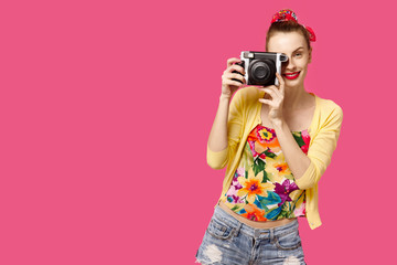 Young girl with camera in hands on a pink background smiling. Colour obsession concept.  Minimalistic style. Stylish Trendy