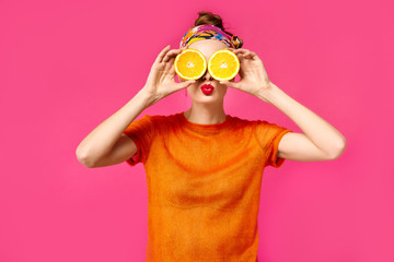 Young woman on a pink background holds a cut orange in her hands and laughs. Colour obsession concept.  Minimalistic style. Stylish Trendy