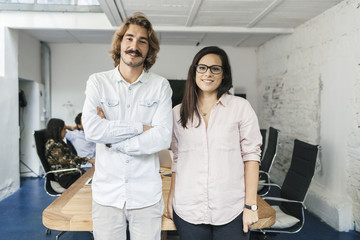 Startup of enterprise. Young business couple looking the camera and smiling during a meeting work in office