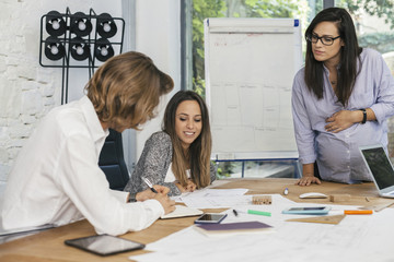 Young pregnant woman at work with his associates in the office during a meeting