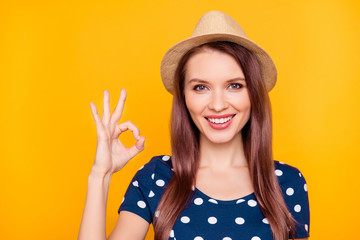 Close up portrait of sexy, charming, pretty, nice, trendy girl in polka-dot t-shirt showing ok sign with fingers, looking at camera, isolated on yellow background