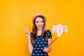 Front view portrait of charming pretty,  confident, successful girl  holding, using selfish stick with smart phone, making selfie, gesture v-sign to the front camera, standing over yellow background