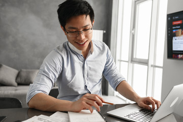 Portrait of a smiling young asian man using laptop computer