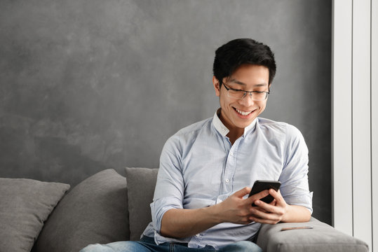 Portrait of a happy young asian man using mobile phone