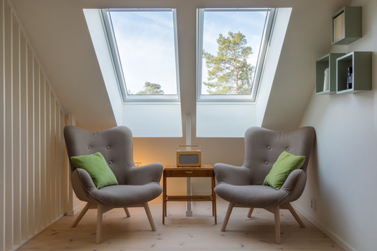 Modern retro design in a attic / loft. Small vintage table with a radio on and two reading chairs under two skylights.