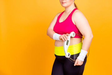 Cropped photo of serious nervous uncertain woman  wearing sport top and leggings pants, she is holding transparent digital bathroom scales in hands, isolated on yellow background, copyspace