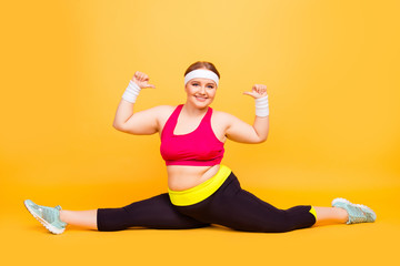 Look at me I can do this! Full-length image of excited cheerful joyful funny cute chubby woman doing splits on the floor and pointing on herself, isolated on yellow background