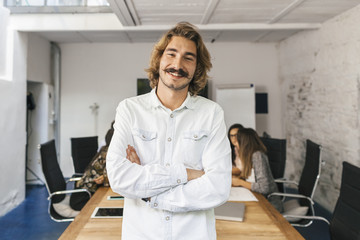 Young businessman looking the camera and smiling during a meeting work in office