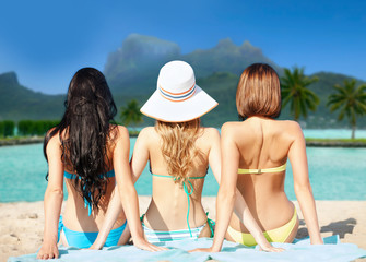 summer holidays, vacation, travel and people concept - group of women in swimwear sunbathing over bora bora island beach background