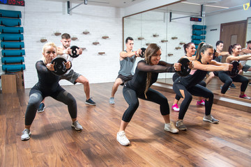 Sporty women and men exercising together with weights in health club.