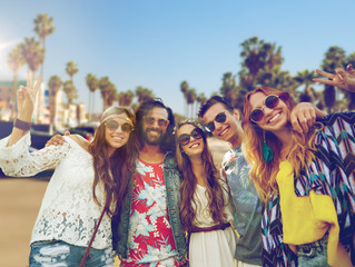 summer holidays, vacation, travel and people concept - smiling young hippie friends showing peace hand sign over venice beach in los angeles background