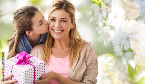 people, holidays and family concept - daughter kissing happy mother and giving her birthday present over cherry blossom background