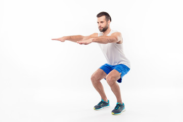 Full-length, half turned portrait of active, sporty, attractive person making, doing squats with straight arms, hands forward, isolated on white background