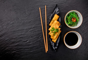 Asian food with spring rolls, seaweed and chopsticks