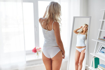 beauty, slimming and people concept - beautiful young woman in white underwear looking at mirror in morning at home