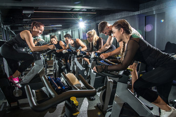 Group of sporty people with their coach training on cycling class in gym