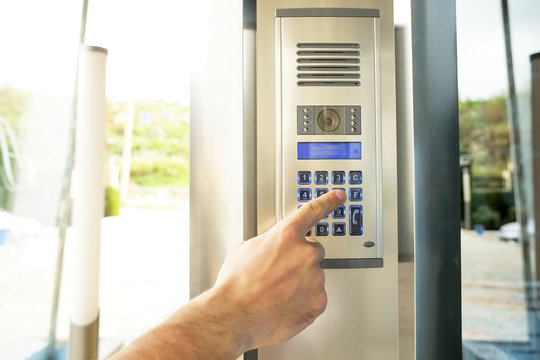 Close up of man hand entering security system code, pressing button with index finger on modern intercom device with blue lcd screen near entrence door. Male opens electronic code lock. Copy space.