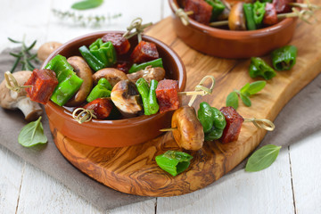 Spanische Pinchos: Brat-Spießchen mit Chorizo-Salami, Pimientos de Padron und Champignons – Spanish snack: Skewer with fried chorizo sausage, pimentos and mushrooms