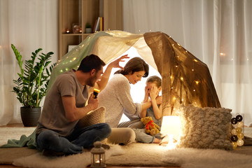 hygge and people concept - father with torch light telling scary stories to his daughter and wife, family having fun in kids tent at night at home Wall mural