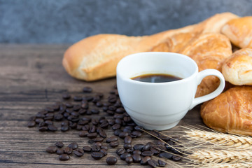Black coffee in white glass placed on a wooden table. Have coffee beans in a bag. Toasted bread and wheat Have breakfast before work.