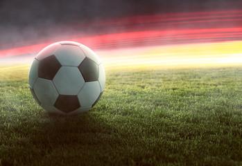 Fußball vor deutschlandfarbenden Lichteffekten