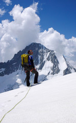 male mountain climber looks towards the summit and his goal while standing o n a high alpine glacier