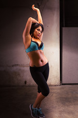Young Pacific Islander woman dressed in athletic clothing in a grungy location
