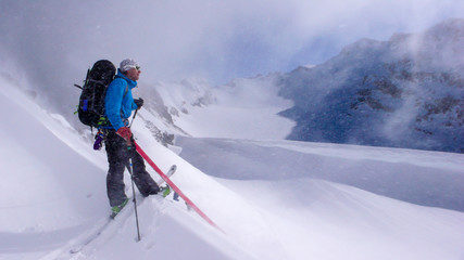 male backcountry skier on a backcountry ski tour playing around during light snowfall on an otherwise beautiful winter day in the Swiss Alps