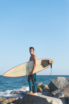 Man with surfboard on coast
