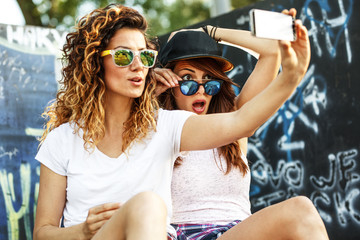 Two female skaters friends sitting on ramp and hangout at the skate park .Taking selfie.