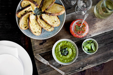 Kale Asiago Pesto Crostini with Quick Pikled Veggies and Basil served with white wine. Photographed on a rustic wood background.