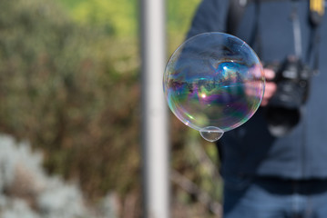 large soap bubble with man carrying camera in background