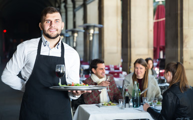 young waiter with serving tray welcoming to restaurant