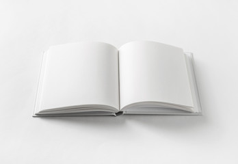 Blank open book on white paper background.