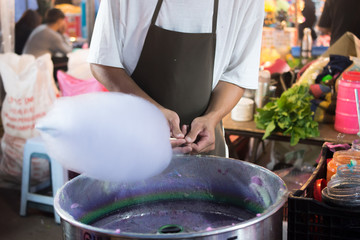Hands of man spinning white cotton candy