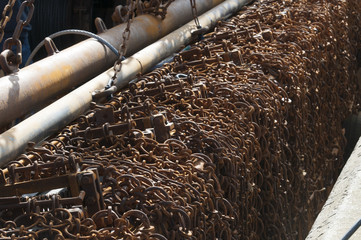 Rusty chains used for raking the sea-bed to disturb flatfish hanging over the edge of a fishing trawler boat.