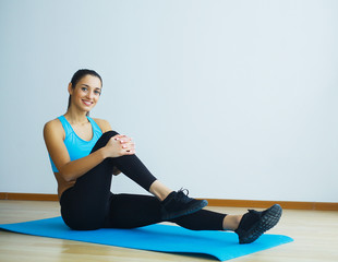 Beautiful smiling woman doing yoga indoors in gym.