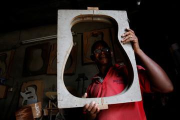 Adicko Pierre, 60, a Ivorian luthier holds a guitar sound box mold at his workshop in Abobo, an area of Abidjan