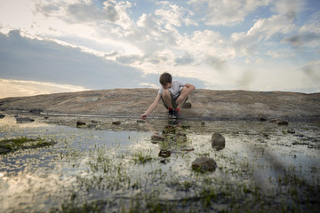 Boy crouching by stream on Arabia Mountain against cloudy sky during sunset