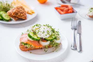 Cereal bun with egg benedict, smoked salmon, sprout micro greens, onion and cucumber slices, cream cheese on the served white wooden table. Healthy breakfast concept. Selective focus.