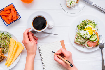 Morning habits of successful people. Day planning and healthy eating. Woman drink coffee and writing in notebook on the served for breakfast white wooden table. Top view, Selective focus.