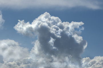 Fluffy white clouds in front of a bright blue sky
