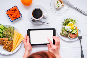 Close up female hands holding tablet with blank copy space screen and having healthy breakfast and coffee. Work, planning, edication during eating. Selective focus, top view.