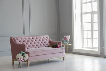 A large beautiful pink sofa stands in a spacious living room in a classic style.
