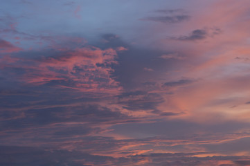 Pink and white cloud in a dark blue sky
