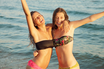 Wet beautiful girls smiling in bikini in the ocean at sunset